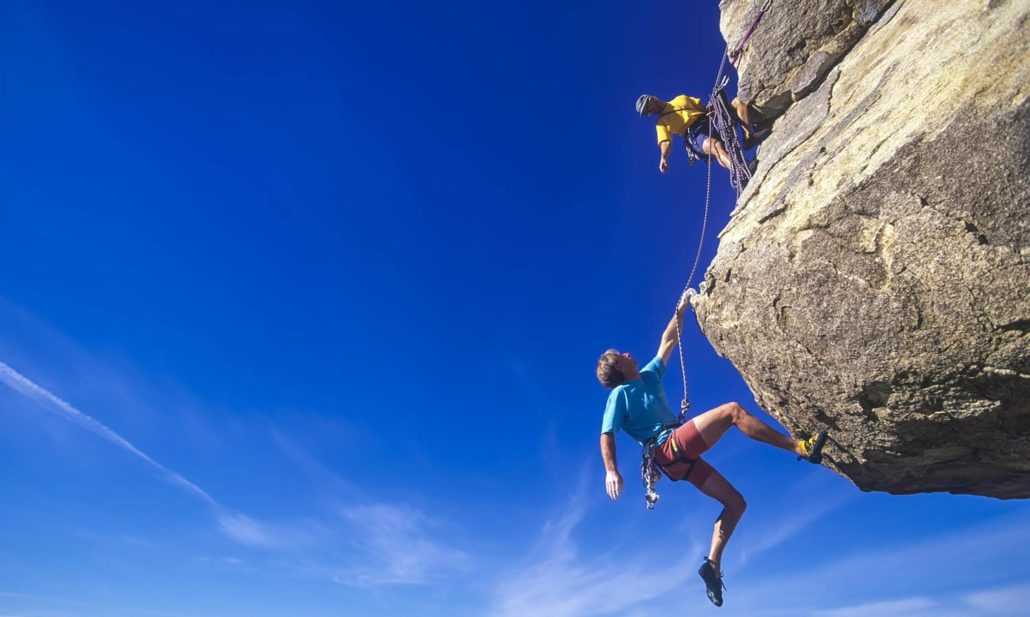 Two rock climbers scale a challenging peak