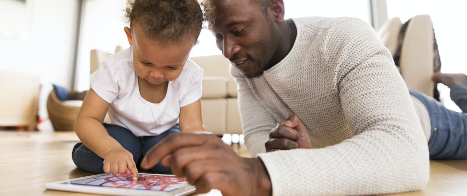 A parent and his toddler explore a digital tablet